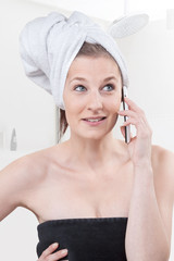 Frau mit Telefon im Badezimmer