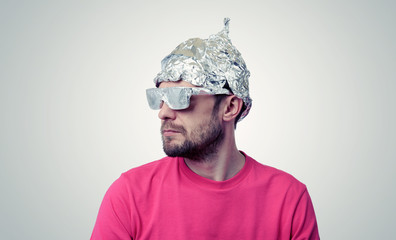 Bearded funny man in a cap of aluminum foil