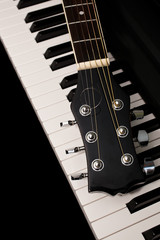 Fragment of a guitar lying on piano keys