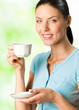 Young happy smiling woman drinking coffee