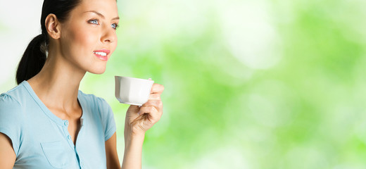 Happy woman drinking coffee, outdoor
