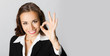 Happy businesswoman with okay gesture, with copyspace