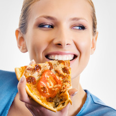 Young woman eating pizza, on grey