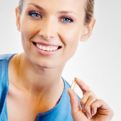 Young woman with Omega 3 fish oil capsule