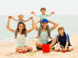 Portrait of happy family with kids on sand