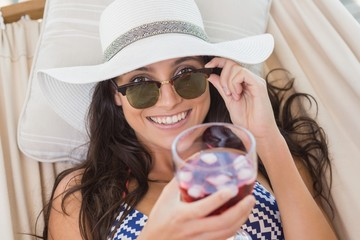 Pretty brunette relaxing on a hammock and drinking cocktail
