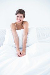 Happy brunette smiling at camera in her bed