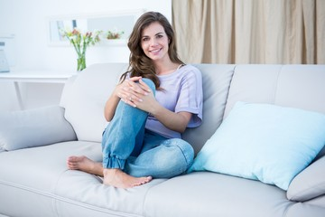 Happy brunette on couch smiling at camera