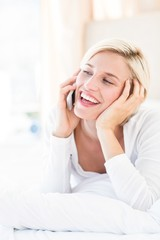 Smiling blonde woman lying on the bed and calling on the phone