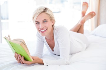 Smiling blonde woman lying on the bed and reading a book