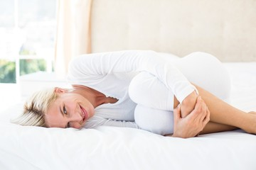 Smiling blonde woman lying on the bed and looking at camera