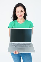 Smiling brunette showing her laptop