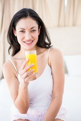 Pretty brunette holding a glass of orange juice on bed