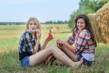 Blonde and brunette girls making soap bubbles in ranch field
