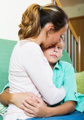 woman comforting crying teenager son