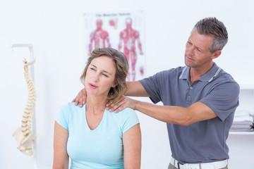 Doctor massaging his patient shoulders