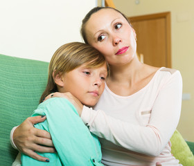 mother consoling crying teenage son at home