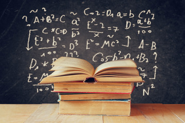 Image of school books on wooden desk over black background with