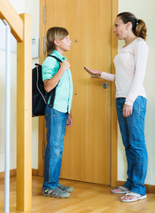 woman lecturing teenager boy before he goes to school