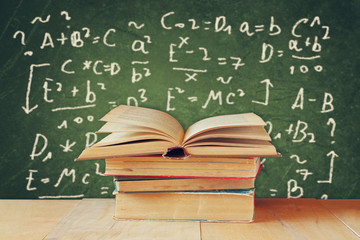 Image of school books on wooden desk over green background with