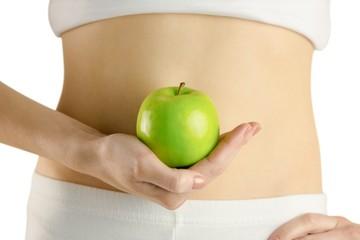 Slim woman holding green apple