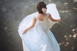 Beautiful bride standing back in her wedding dresss - 82094338