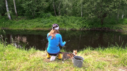 blond woman fishing on pond shore with cute cat pet