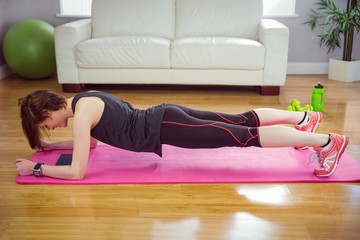 Fit woman doing plank on mat