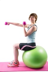 Pretty brunette exercising with dumbbells on fitness ball
