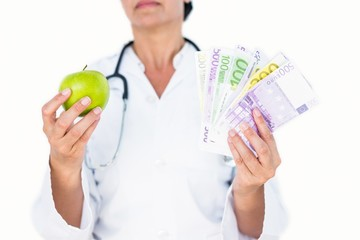 Confident female doctor holding green apple and banknotes