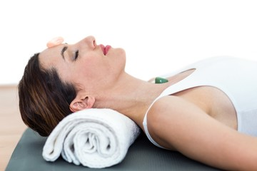 Relaxed brunette lying on mat with stones
