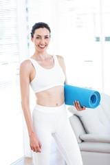Smiling brunette holding exercise mat