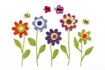 gehäkelte Blumen mit Schmetterlingen und Bienen
