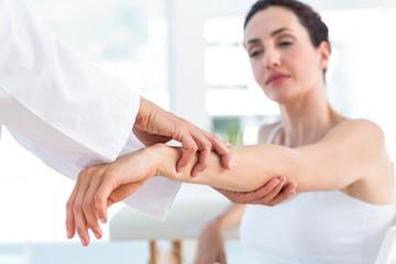 Doctor examining her patients elbow
