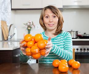 woman holding  heap of mandarins