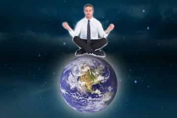 Composite image of businessman meditating in lotus pose