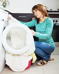 Unhappy  housewife near washing machine