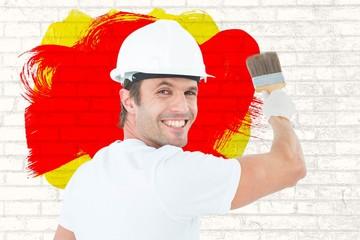 Composite image of portrait of happy man using paintbrush