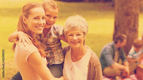 Grandmother mother and daughter with family in background - 82098153