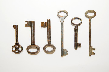 Six old keys to the safe on a white background