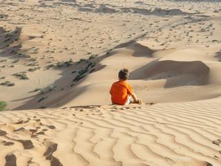 Kaukasischer Junge sitzt auf Sanddüne Rückansicht
