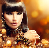 Fashion model brunette girl with golden accessories