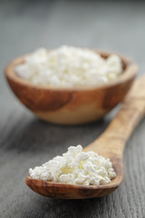 fresh cottage cheese in a wood bowl on a wooden table