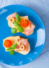 Small sandwiches with smoked ham, cheese and cherry tomato