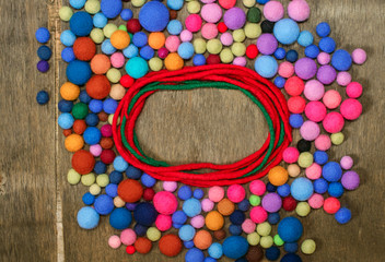 Red circle and multicolored beads made of wool merino