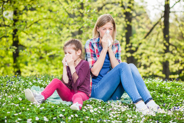 Two people with allergy symptom blow their noses