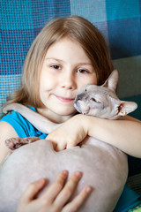 Pretty preschool age girl embracing sphynx cat at couch