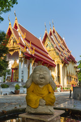 little monk statue close his ear with temple background