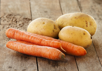 Young potatoes and carrots on wooden background close up
