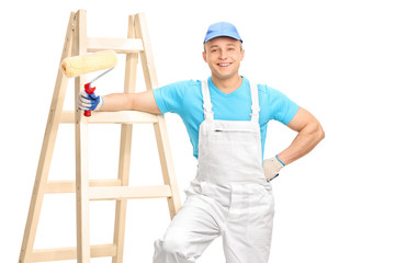Cheerful male decorator holding a paint roller